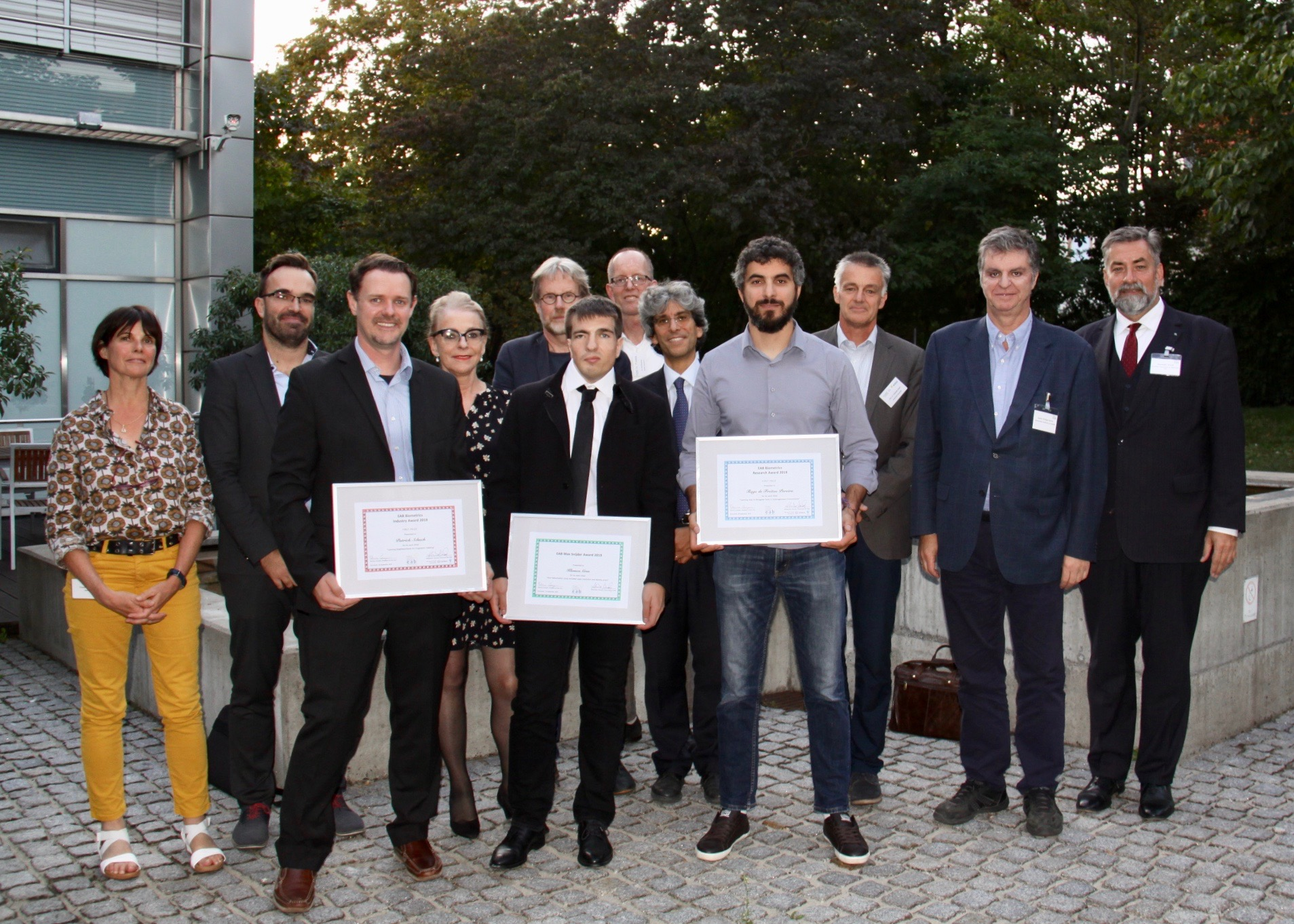 [Photo] The winners of the European Biometrics Max Snijder, Research, and Industry Awards 2019 Patrick Schuch, Klemen Grm and Tiago de Freitas Pereira together with Claude Bauzou (IDEMIA), Vitomir Struc (University of Ljubljana), Marianne Volonte (mymarc), Raymond Veldhuis (University of Twente), Tom Kevenaar (GenKey), Patrizio Campisi (University University of Roma TRE), Christoph Busch (Norwegian University of Science and Technology) and Alexander Nouak (EAB chair)